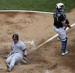New York Yankees' Luke Voit, left, scores on a two-run single by Brett Gardner as Chicago White Sox catcher James McCann looks to the field during the third inning of a baseball game in Chicago, Sunday, June 16, 2019. (AP Photo/Nam Y. Huh)