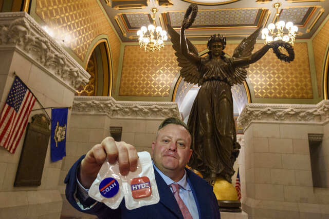 U.S Congressional candidate Robert Hyde of Simsbury displays campaign phone-grips under the Genius of Connecticut statue in the Connecticut State Capitol Friday, Jan. 17, 2020. Documents released this week by House Democrats link Hyde to alleged campaign to surveil and harass Marie Yovanovitch, the former U.S. ambassador to Ukraine. (Mark Mirko/Hartford Courant via AP)