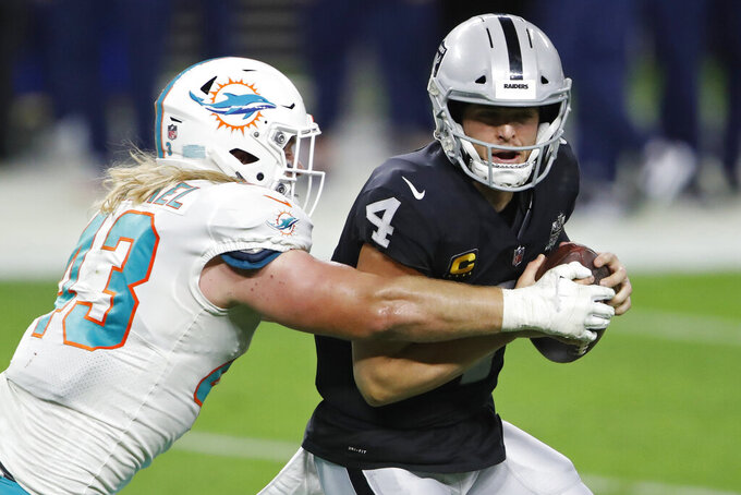 Miami Dolphins outside linebacker Andrew Van Ginkel (43) tackles Las Vegas Raiders quarterback Derek Carr (4) during the first half of an NFL football game, Saturday, Dec. 26, 2020, in Las Vegas. (AP Photo/Steve Marcus)