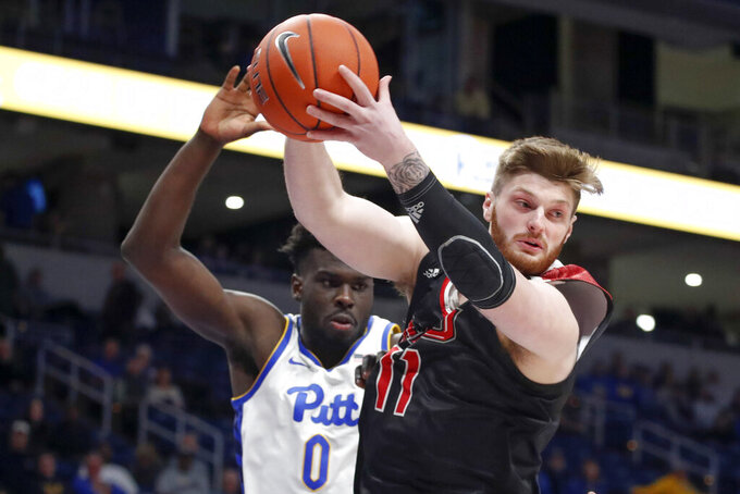 Northern Illinois's Noah McCarty (11) grabs a rebound in front of Pittsburgh's Eric Hamilton (0) during the first half of an NCAA college basketball game, Monday, Dec. 16, 2019, in Pittsburgh. (AP Photo/Keith Srakocic)