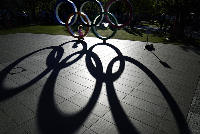 A child sits in the Olympic rings on display outside the Olympic Stadium where the athletic events are underway at the 2020 Summer Olympics, Tuesday, Aug. 3, 2021, in Tokyo. (AP Photo/David Goldman)