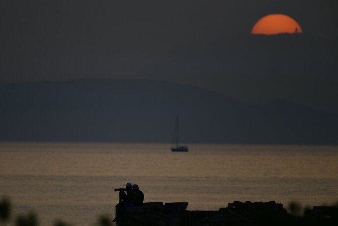 Two men sit on a rock as the sun sets, near a beach of Kavouri suburb, southwest of Athens, Greece, Monday, Aug. 2, 2021. The heat wave is expected to peak Monday, with temperatures inland ranging from 42 to 46 degrees Celsius (107.6 to 114.8 Fahrenheit). Temperatures will remain at 40 Celsius (104 Fahrenheit) or above in much of Greece until at least Friday, meteorologists say. (AP Photo/Michael Varaklas)