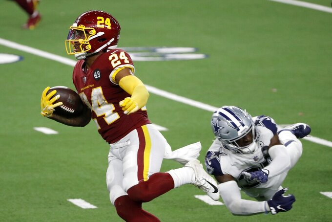 Washington Football Team running back Antonio Gibson (24) gets past a tackle attempt by Dallas Cowboys safety Donovan Wilson (37) on a touchdown run in the second half of an NFL football game in Arlington, Texas, Thursday, Nov. 26, 2020. (AP Photo/Roger Steinman)