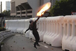 An anti-government protester throws a Molotov cocktail during a demonstration near Central Government Complex in Hong Kong, Sunday, Sept. 15, 2019. Police fired a water cannon and tear gas at protesters who lobbed Molotov cocktails outside the Hong Kong government office complex Sunday, as violence flared anew after thousands of pro-democracy supporters marched through downtown in defiance of a police ban. (AP Photo/Kin Cheung)