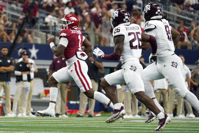 Arkansas quarterback KJ Jefferson (1) runs the ball as Texas A&M defensive back Demani Richardson (26) and defensive lineman DeMarvin Leal (8) give chase in the first half of an NCAA college football game in Arlington, Texas, Saturday, Sept. 25, 2021. (AP Photo/Tony Gutierrez)