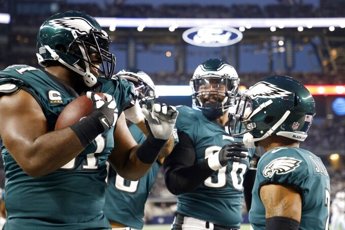 Philadelphia Eagles defensive tackle Fletcher Cox, left, celebrates with teammates after recovering a Dallas Cowboys fumble in the end zone for a touchdown in the first half of an NFL football game in Arlington, Texas, Monday, Sept. 27, 2021. (AP Photo/Michael Ainsworth)