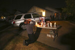 In this photo taken Monday, Nov. 18, 2019, Neej Xiong, uncle of shooting victim Kour Xiong, prays in front of a memorial during a candlelight vigil in Fresno, Calif. A close-knit Hmong community was in shock after gunmen burst into a California backyard gathering and shot 10 men, killing four.