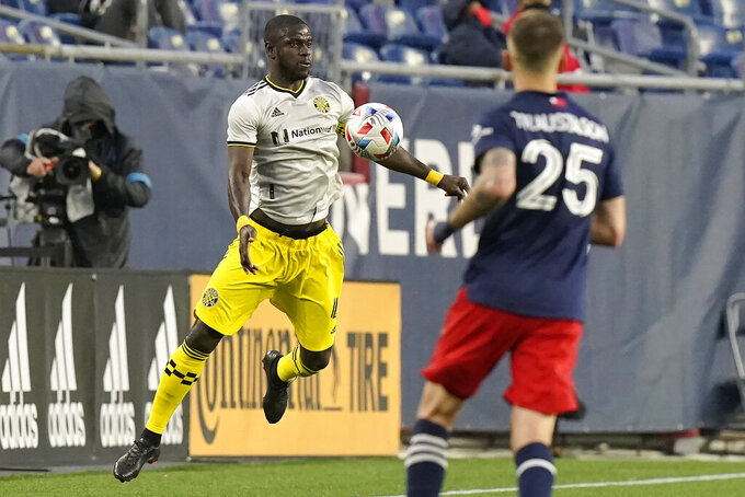Columbus Crew's Jonathan Mensah, left, and New England Revolution's Arnor Traustason, right, vie for control of the ball in the second half of an MLS Soccer match, Sunday, May 16, 2021, in Foxborough, Mass.  (AP Photo/Steven Senne)
