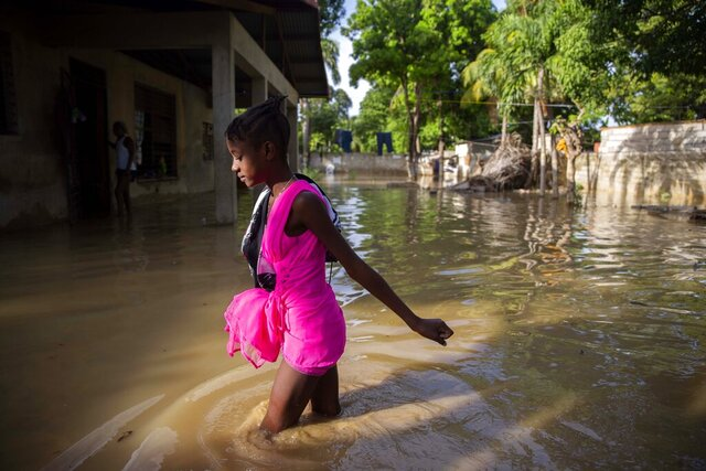 A girl wades towards her flooded home the day after the passing of Tropical Storm Laura in Port-au-Prince, Haiti, Monday, Aug. 24, 2020. Laura battered the Dominican Republic and Haiti on it's way to the U.S. Gulf Coast, where forecaster fear it could become a major hurricane. (AP Photo/Dieu Nalio Chery)