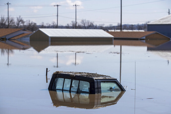 The cab of a pickup truck peeks out of floodwaters Wednesday, March 20, 2019, in Hamburg, Iowa. As some communities along the Missouri River start to shift their focus to flood recovery after a late-winter storm, residents in two Iowa cities are still in crisis mode because their treatment plants have shut down and they lack fresh water. (Chris Machian/Omaha World-Herald via AP)