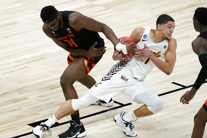 Loyola Chicago guard Lucas Williamson (1) fights for a loose ball with Oregon State forward Rodrigue Andela (34) during the second half of a Sweet 16 game in the NCAA men's college basketball tournament at Bankers Life Fieldhouse, Saturday, March 27, 2021, in Indianapolis. (AP Photo/Darron Cummings)