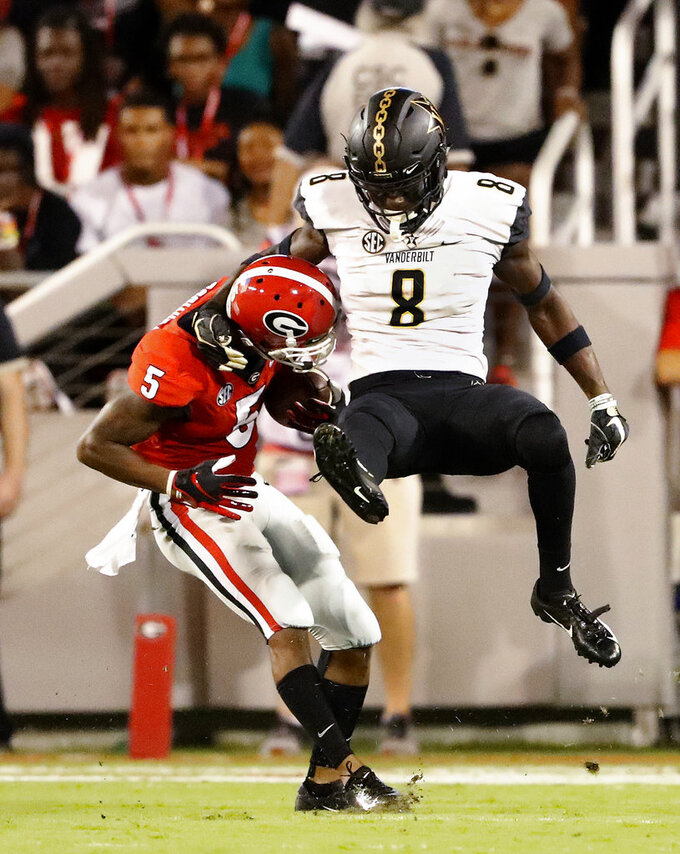 Georgia wide receiver Terry Godwin (5) gets away from Vanderbilt cornerback Joejuan Williams (8) to score a touchdown after catching a pass from quarterback Jake Fromm during the first half of an NCAA college football game Saturday, Oct. 6, 2018, in Atlanta. (AP Photo/John Bazemore)