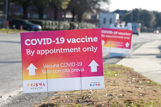 Signs line the pathway to a COVID-19 vaccine site operated by PRISMA Health in Columbia, S.C., on Tuesday, Feb. 9, 2021. (AP Photo/Meg Kinnard)