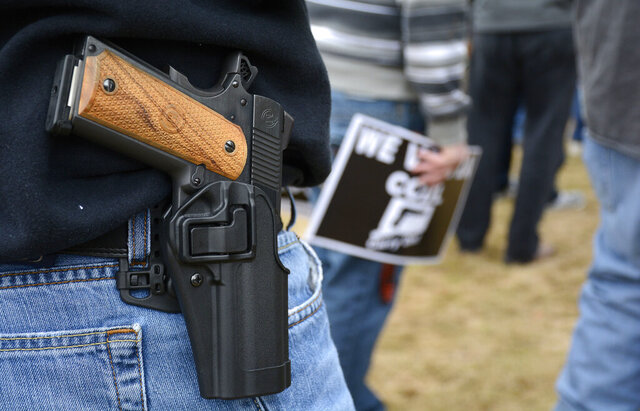 FILE - In this April 5, 2014, file photo, a man open carries a 1911 handgun while at a CCDL gun rights rally at the Connecticut state capitol in Hartford. The Democratic co-chairmen of the Judiciary Committee, Sen. Gary Winfield and Rep. Steve Stafstrom, have introduced a bill to revamp Connecticut's 1999
