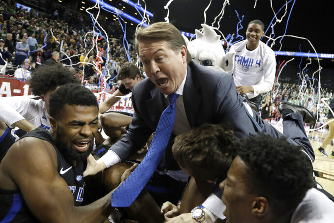 Saint Louis coach Travis Ford leaps over players to jump onto the pile, celebrating after Saint Louis defeated St. Bonaventure during an NCAA college basketball game in the final of Atlantic 10 men's tournament Sunday, March 17, 2019, in New York. Saint Louis won 55-53. (AP Photo/Julio Cortez)