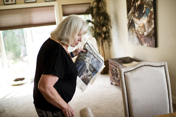 Mandy deGignac, a flight attendant on the first flight into New York City on Sept. 14, 2001, after the attacks on 9/11, holds an original copy of the San Francisco Chronicle from the attack, on Sept. 2, 2021, in Bozeman, Mont. On the front page is a photograph of the towers falling. (Rachel Leathe/Bozeman Daily Chronicle via AP)