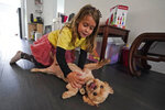 Anabelle Chao plays with her dog Poochi after finishing remote learning for the day, Thursday, Oct. 1, 2020, at her home in North Miami Beach, Fla. Rather than wait to see how the Miami-Dade school system would handle instruction this fall, Erica Chao enrolled her two daughters in a private school that seemed better positioned to provide remote learning than their public elementary school was when the coronavirus first reached Florida. (AP Photo/Wilfredo Lee)