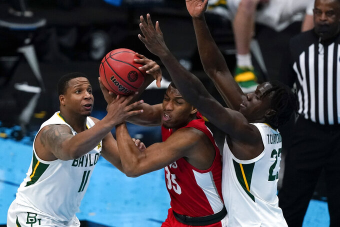 Houston forward Fabian White Jr. (35) passes between Baylor guard Mark Vital (11) and forward Jonathan Tchamwa Tchatchoua, right, during the first half of a men's Final Four NCAA college basketball tournament semifinal game, Saturday, April 3, 2021, at Lucas Oil Stadium in Indianapolis. (AP Photo/Michael Conroy)