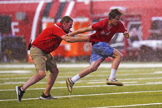 A spectator, right, is dragged down after he ran on to the field during a rain delay during the first half of an NCAA college football game between Weber State and Utah on Thursday, Sept. 2, 2021, in Salt Lake City. (AP Photo/Rick Bowmer)