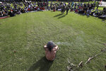 An Aboriginal man sits with a small fire during a traditional smoking ceremony as thousands gather at a rally supporting the Black Lives Matter and Black Deaths in Custody movements in Sydney, Sunday, July 5, 2020. (AP Photo/Rick Rycroft)