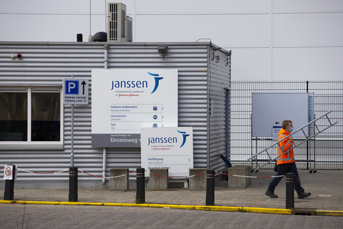 A man passes the entrance of the Janssen Pharmaceuticals company, which is owned by Johnson & Johnson, in Leiden, Netherlands, Wednesday, April 14, 2021. European nations from across the continent are scrambling to react to Johnson & Johnson's delay of the rollout for its COVID-19 vaccine amid reports of rare blood clots. (AP Photo/Peter Dejong)