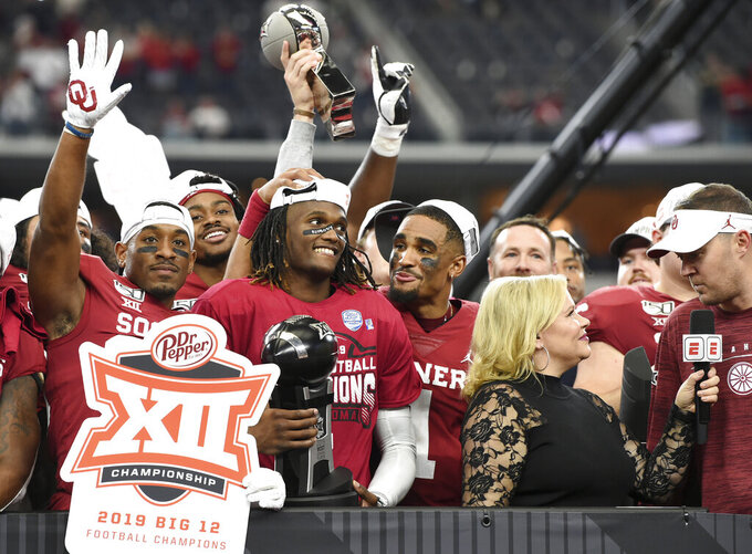 Oklahoma wide receiver CeeDee Lamb, center, holds the Most Outstanding Player award as he is congratulated by quarterback Jalen Hurts (1) after their 30-23 overtime victory over Baylor in an NCAA college football game for the Big 12 Conference championship, Saturday, Dec. 7, 2019, in Arlington, Texas. (AP Photo/Jeffrey McWhorter)
