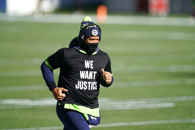 "Seattle Seahawks quarterback Russell Wilson wears a T-shirt that reads ""We Want Justice"" in support of Black Lives Matter before an NFL football game against the San Francisco 49ers, Sunday, Nov. 1, 2020, in Seattle. (AP Photo/Elaine Thompson)"