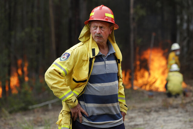 Doug Schutz, the Tomerong Rural Fire Service Captain, oversees a controlled burn near Tomerong, Australia, Wednesday, Jan. 8, 2020, set in an effort to contain a larger fire nearby. Schutz began volunteering with the Rural Fire Service in New South Wales some 53 years ago, at the age of 13. That was back in the days when the fire truck was a Land Rover that towed a trailer with a water pump on top. Schutz is part of an army of 72,000 people from across the state who make up the world's largest volunteer fire service. (AP Photo/Rick Rycroft)