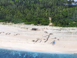 In this photo provided by the Australian Defence Force, three men stand the beach on Pikelot Island in the Federated States of Micronesia Sunday, Aug. 2, 2020, where they are found safe and healthy after missing for three days. The men were missing in the Micronesia archipelago east of the Philippines for nearly three days when their