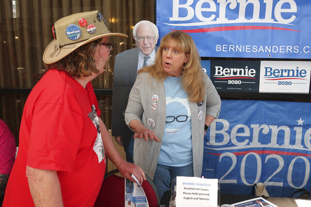 In this Saturday, March 7, 2020 photo, Kansas supporters of Vermont Sen. Bernie Sanders, Ron Rose, left, of Topeka, and Judy Johnson, right, of Olathe, talk in front of table for Sanders' presidential campaign during a Kansas Democratic Party convention in Topeka, Kan. The Kansas Democratic Party has scrapped its plans to have polling sites for the state's presidential primary and will conduct the election only by mail ballots due to coronavirus concerns. (AP Photo/John Hanna)