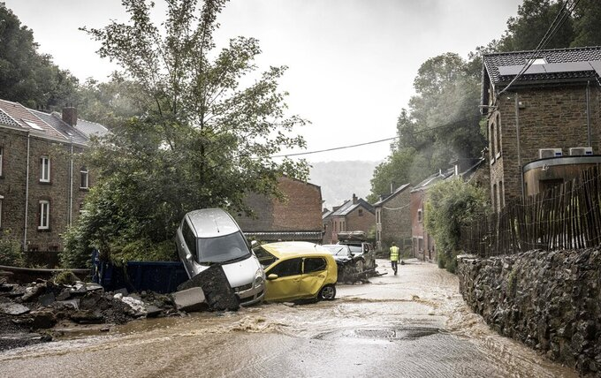 A man walks by damaged cars in a flooded street in Mery, Province of Liege, Belgium, Wednesday, July 14, 2021. A code red was issued in parts of Belgium on Wednesday as severe rains hit the area. (AP Photo/Valentin Bianchi)