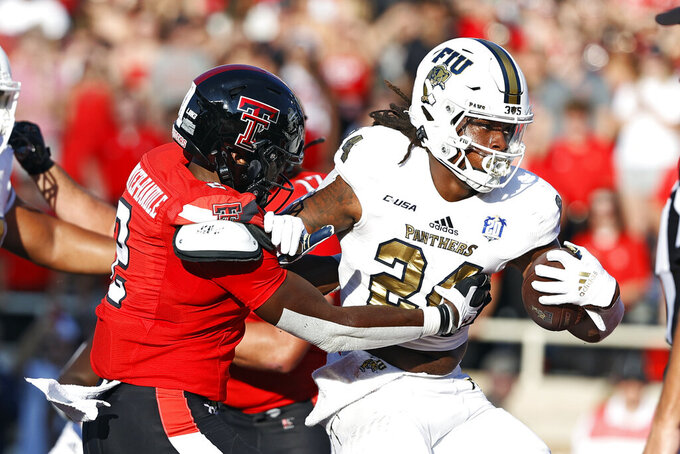 Florida International's D'vonte Price (24) breaks away from Texas Tech's Brandon Bouyer-Randle (2) to score a touchdown during the first half of an NCAA college football game on Saturday, Sept. 18, 2021, in Lubbock, Texas. (AP Photo/Brad Tollefson)