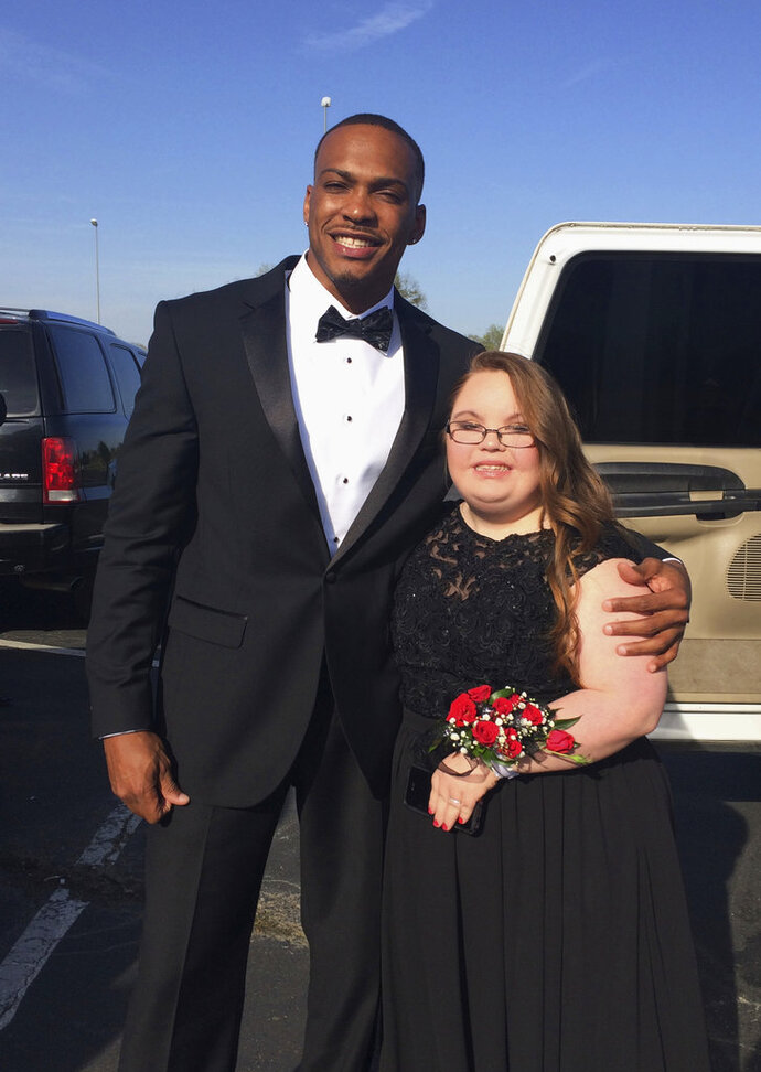 CORRECTS NAME IN ALL REFERENCES TO KRISTI MARTIN NOT PRESTON This photo taken April 13, 2018 by Kristi Martin, shows her daughter Lindsey Preston, next to NFL player Don Jones at Preston's prom in Moulton, Ala. Jones a defensive back for the San Francisco 49ers, took Preston, who has Down Syndrome to the county-wide event for high school students with special needs. (Kristi Martin via AP)