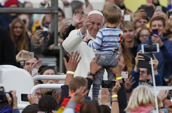 Pope Francis reaches out to greet a child during his meeting with youths at the Cathedral Square in Vilnius, Lithuania, Saturday Sept. 22, 2018. Pope Francis begins a four-day visit to the Baltics amid renewed alarm about Moscow's intentions in the region it has twice occupied. (AP Photo/Mindaugas Kulbis)