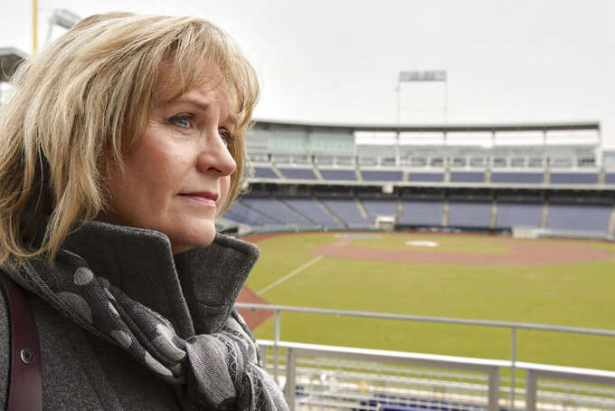 In this March 23, 2020, photo, Kathryn Morrissey, Executive Director of College World Series Inc., speaks in Omaha, Neb., during an interview with the Associated Press, with TD Ameritrade Park, home of the College World Series, behind her. The Division I baseball championship, decided in this city of just under a half-million for the past 70 years, is among the many sporting events canceled or postponed because of the coronavirus pandemic. (AP Photo/Nati Harnik)