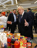 Britain's Prime Minister Boris Johnson speaks to staff and students at Bolton University, in Bolton, England, Saturday Nov. 16, 2019, in the aftermath of a major blaze which damaged a student residential building late Friday.  A large fire broke out in a student accommodation block of flats known as The Cube late Friday, resulting in two people being treated at the scene.  Visiting the scene, Johnson broke from his election campaign trail ahead of the Dec. 12 General Election. (Christopher Furlong/pool via AP)