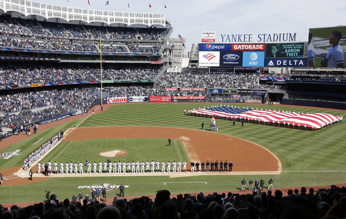 FILE - In this March 28, 2019, file photo, a large flag is unfurled during the national anthem before an opening day baseball game between the New York Yankees and the Baltimore Orioles at Yankee Stadium in New York. Forbes estimates the New York Yankees are baseball's most valuable franchise at $5 billion, up 9% over last year and 47% more than the No. 2 Los Angeles Dodgers at $3.4 billion.(AP Photo/Seth Wenig, File)