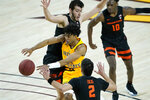 Arizona State guard Remy Martin dishes off as Oregon State guard Jarod Lucas (2) and center Roman Silva defend during the second half of an NCAA college basketball game, Sunday, Feb. 14, 2021, in Tempe, Ariz.(AP Photo/Matt York)