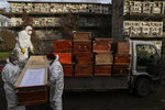 Workers collect and stack the coffins of people that have been recently cremated amid the new coronavirus pandemic, at the La Recoleta cemetery in Santiago, Chile, Sunday, June 28, 2020. The coffins are collected, destroyed, and processed by a company specialized in organic waste. (AP Photo/Esteban Felix)