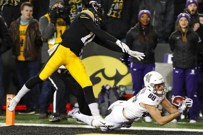 Northwestern wide receiver Bennett Skowronek catches a 32-yard touchdown pass ahead of Iowa defensive back Michael Ojemudia, left, during the second half of an NCAA college football game, Saturday, Nov. 10, 2018, in Iowa City, Iowa. Northwestern won 14-10. (AP Photo/Charlie Neibergall)