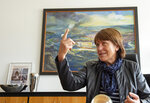 In this Wednesday, May 15, 2019, Pia Findeiss, Zwickau's Lord of Mayor, gestures in front of an oil painting from the 1980s during an interview with the Associated Press in the city hall in Zwickau, Germany. Volkswagen will total shift into electric cars at the plant in Zwickau and the first vehicles are to roll off the assembly line at the end of 2019. (AP Photo/Jens Meyer)