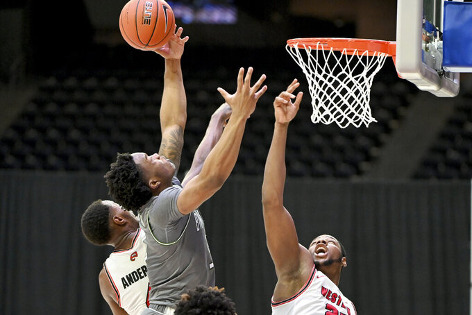 Western Kentucky guard Josh Anderson, left,and center Charles Bassey (23) defend on a shot by UAB guard Tavin Lovan, center, in the second half of an NCAA college basketball game in the Conference USA men's tournament, in Frisco, Texas, Friday, March 12, 2021. Western Kentucky won 64-60. (AP Photo/Matt Strasen)