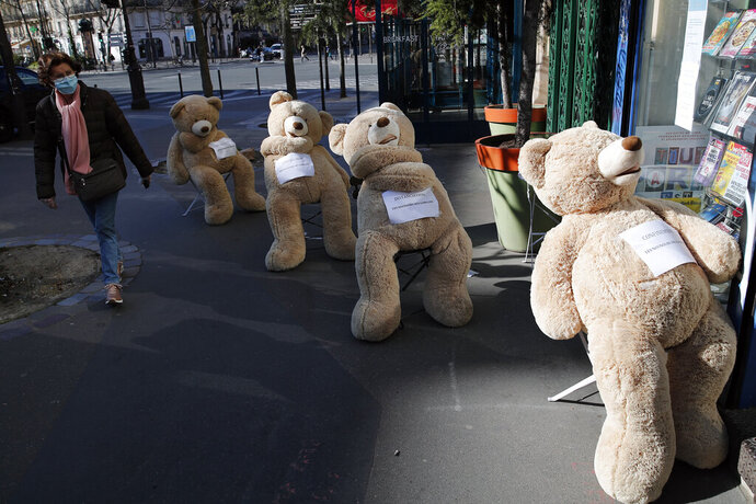 A woman wearing a protective mask walks by a shop with bears installed in line to show social distancing in Paris, Tuesday, March 24, 2020. French President Emmanuel Macron urged employees to keep working in supermarkets, production sites and other businesses that need to keep running amid stringent restrictions of movement due to the rapid spreading of the new coronavirus in the country. For most people, the new coronavirus causes only mild or moderate symptoms. For some it can cause more severe illness, especially in older adults and people with existing health problems. (AP Photo/Francois Mori)