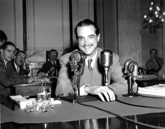 FILE - In this Nov. 15, 1947, file photo, Howard Hughes smiles as he sits in the witness chair before reading a statement at the Senate War Investigation Subcommittee hearing in Washington, D.C.  Four-time and retired NASCAR champion Jeff Gordon was an obvious choice for the Motorsports Hall of Fame. One of his fellow inductees seemed like a totally random selection. Some might even think his name was plucked out of thin air. Gordon and record-setting pilot and eccentric billionaire Howard Hughes were among seven people selected for the Motorsports Hall of Fame of America. The 2018 class was announced Friday, Jan. 5, 2018,  at Daytona International Speedway. (AP Photo/File)