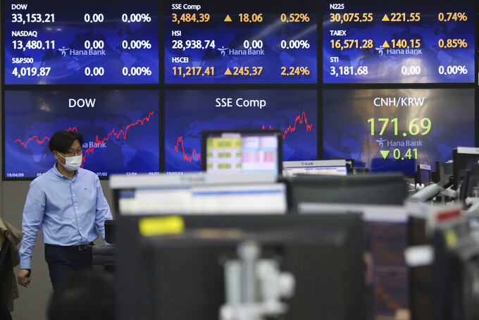A currency trader passes by screens showing foreign exchange rates at the foreign exchange dealing room of the KEB Hana Bank headquarters in Seoul, South Korea, Monday, April 5, 2021. Asian stock markets were mostly higher Monday after Wall Street hit a record high on optimism the spread of coronavirus vaccines might allow global business to return to normal.(AP Photo/Ahn Young-joon)
