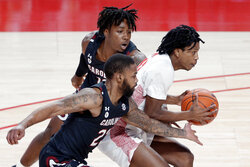 Houston guard Tramon Mark, right, drives to the basket in front of South Carolina guard Seventh Woods (23) and guard Trae Hannibal, back, during the first half of an NCAA college basketball game Saturday, Dec. 5, 2020, in Houston. (AP Photo/Michael Wyke)