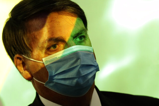 Brazil's President Jair Bolsonaro wears a mask amid the COVID-19 pandemic at the start of a ceremony where his nation's flag is projected in Brasilia, Brazil, Wednesday, Aug. 5, 2020. (AP Photo/Eraldo Peres)