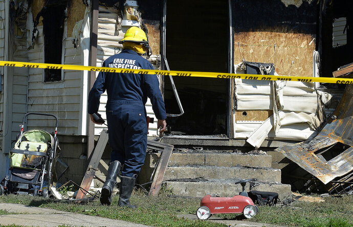 File-This Aug. 11, 2019, file photo shows Erie Bureau of Fire Inspector Mark Polanski helping investigate a fatal fire at 1248 West 11th St. in Erie, Pa. Investigators are blaming an electrical extension cord for a fire that killed five small children two months ago in Pennsylvania. The investigative team said Thursday, Oct. 10, 2019, that the deadly Aug. 11 fire at the Erie, Pennsylvania, home that included the Harris Family Daycare was an accident, caused by an electrical failure associated with the routinely used cord. (Greg Wohlford/Erie Times-News via AP, File)