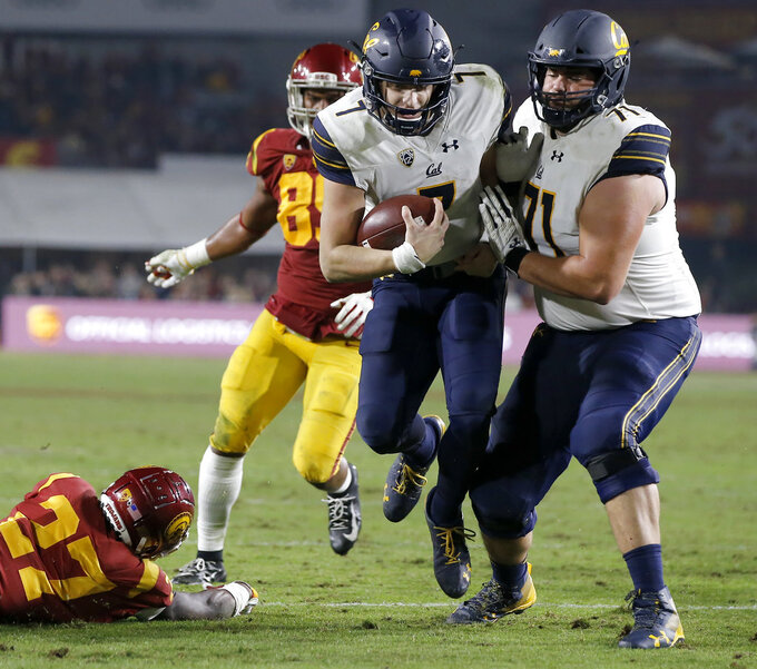 California quarterback Chase Garbers, center, collides with right tackle Jake Curhan, right, after stepping past Southern California cornerback Ajene Harris, left, and defensive lineman Christian Rector, second from left, en route to score during the second half of an NCAA college football game in Los Angeles, Saturday, Nov. 10, 2018. California won 15-14. (AP Photo/Alex Gallardo)