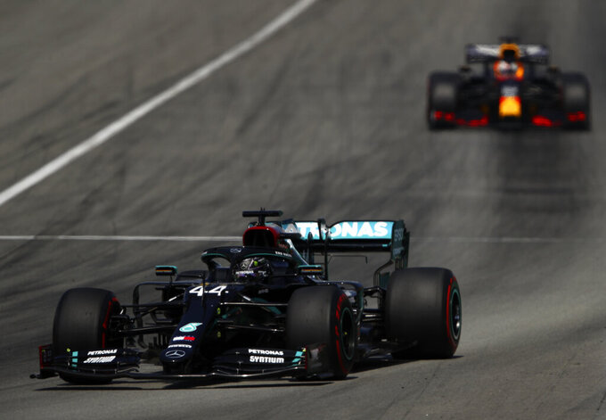 Mercedes driver Lewis Hamilton of Britain steers his car followed by Red Bull driver Max Verstappen of the Netherlands during the Formula One Grand Prix at the Barcelona Catalunya racetrack in Montmelo, Spain, Sunday, Aug. 16, 2020. (Bryn Lennon, Pool via AP)